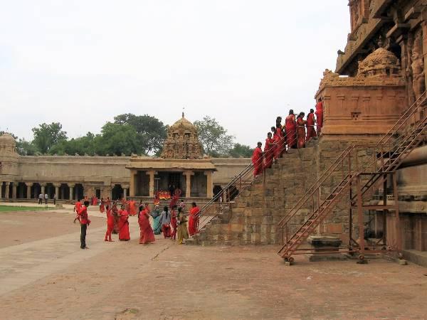 Pélerine habillés en rouge qui montent un escalier sur un temple
