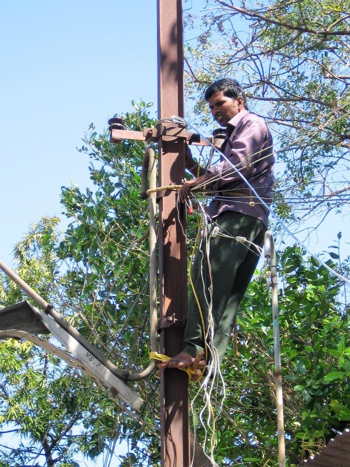 Inde homme qui touche des fils électriques sur un poteau
