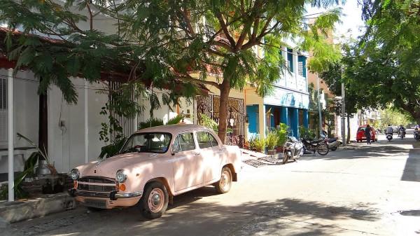 Veille voiture rose pâle dans une rue ombragée
