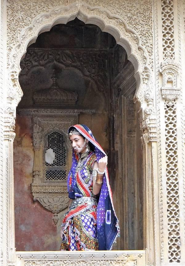 Inde Rajasthan jeune femme en sari posant sous une porte sculptée