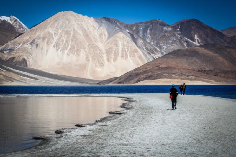 Hommes marchant au bord d'un lac sur fond de montagnes