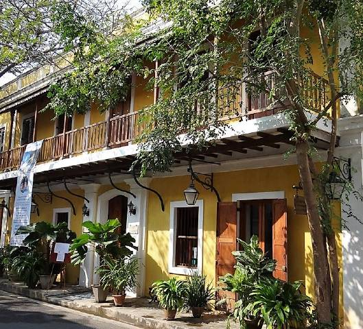 Maison coloniale jaune avec verdure