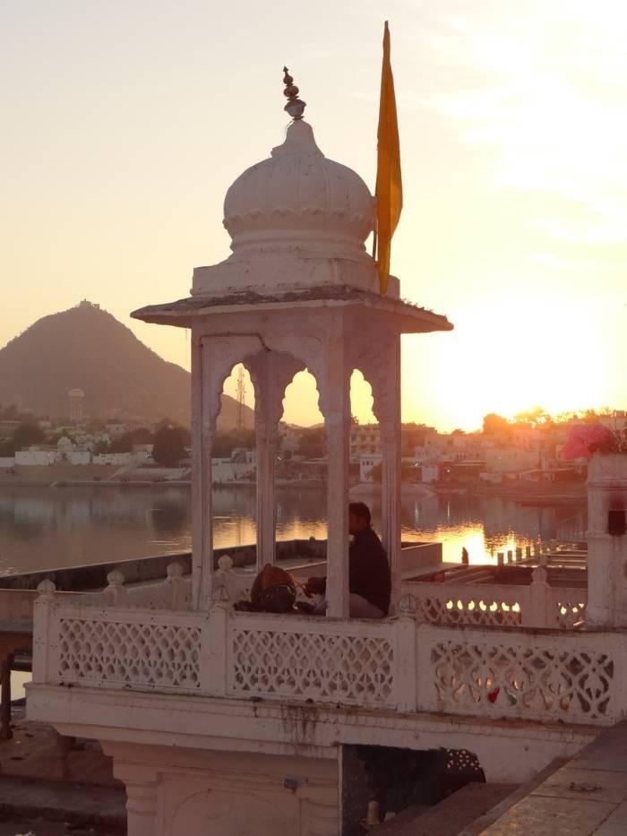 Inde tourelle blanche sir coucher de soleil avec un homme assis