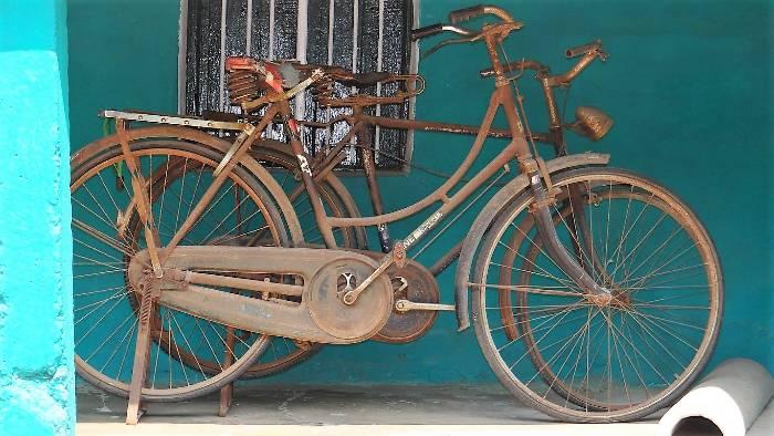 Vieux vélos rouillés devant une mur bleu