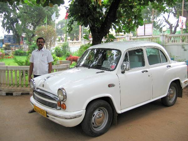 Vieille voiture blanche avec un chauffeur indien