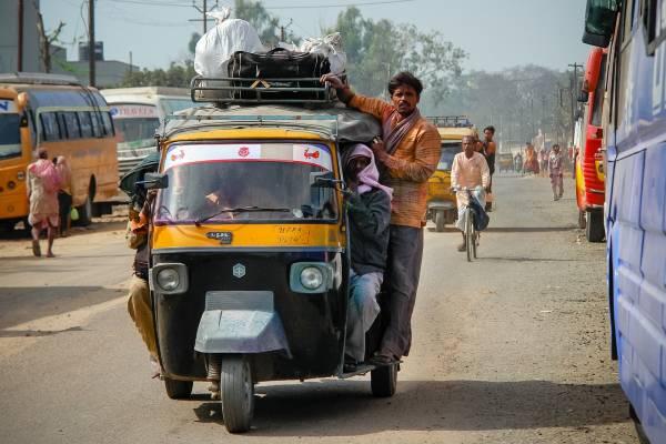 Inde tuk-tuk avec un homme accroché à l'extérieur