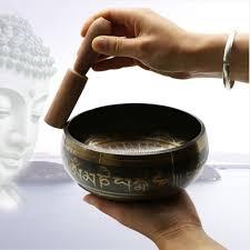 Inde bol en bronze qui fait de la musique avec un bâton de bois