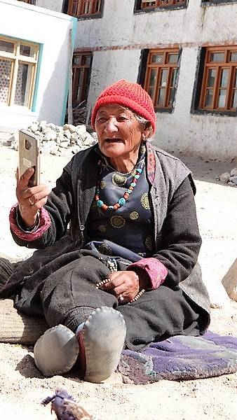 Ladakh >>>Grand-Mère assise par terre avec 1 téléphone portable