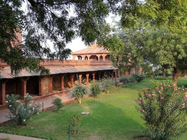 Inde cloître grès rouge autour d'un carré de jardin