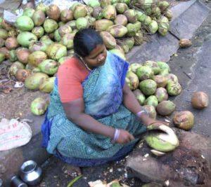 Femme coupant une noix de coco